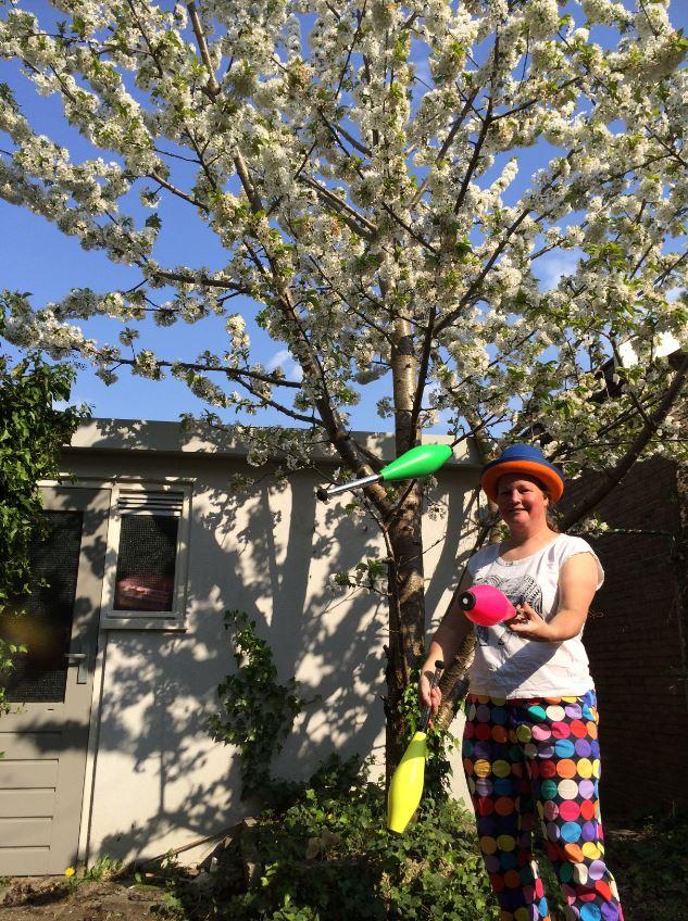 Jongleur Kiko ana het jongleren voor een kersenboom