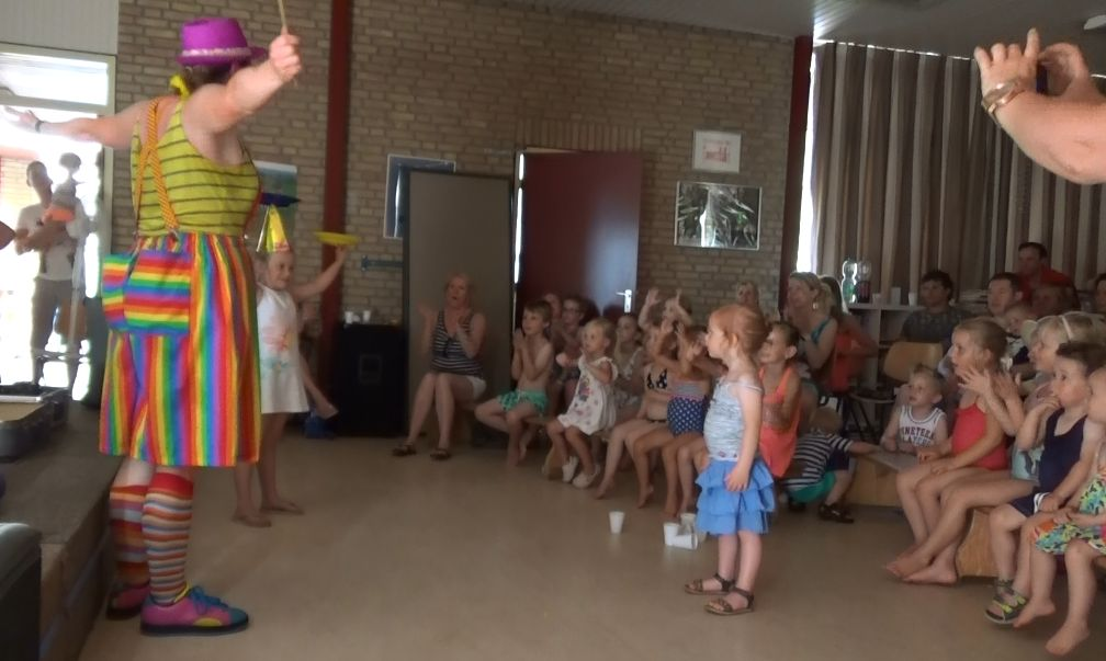 Clown kiko krijgt hulp van een van de peuters bij het draaien van een chinees bordje in een Peutervoorstelling Kindertheater Kiko bij een peuterspeelzaal