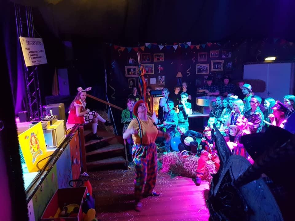 Clown Kiko balanceert een paraplu op haar kin tijdens de kindercarnaval in Maren kessel