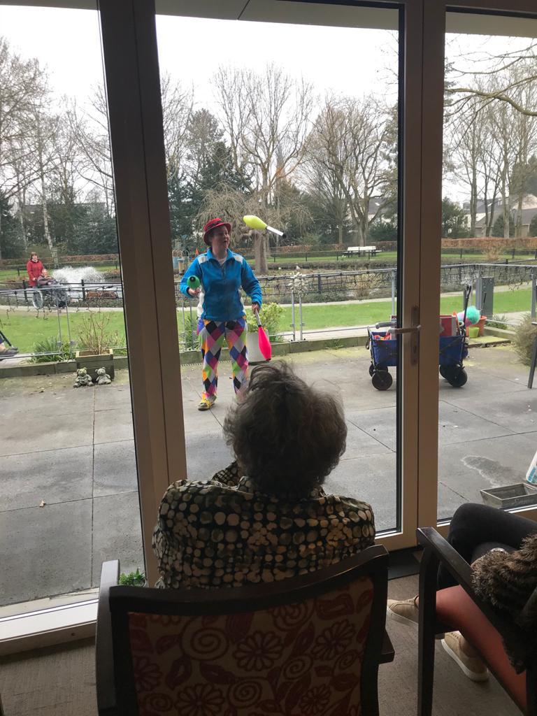 Jongleur Kiko corona-proof optreden voor ouderen in een verpleeghuis optreden met het raam ertussen  Kiko buiten en het publiek binnen