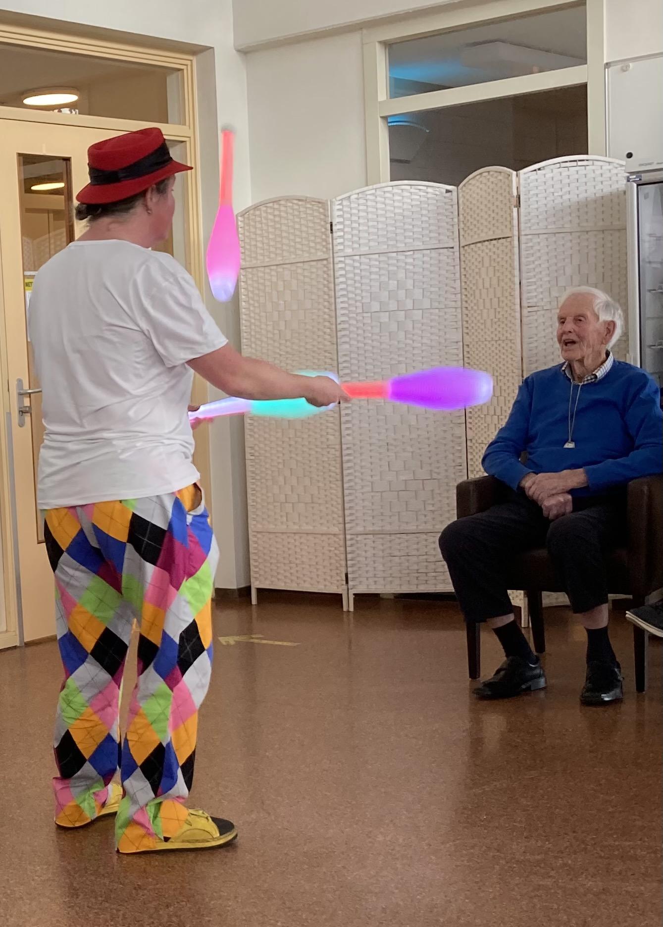 Jongleur Kiko aan het jongleren met lichtgevende kegels in een leuke, interactieve en verassende corona-proof jongleershow voor ouderen in verpleeghuizen